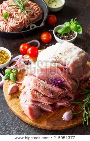 Fresh different raw meat and minced meat on a stone or slate background.