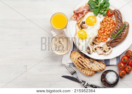 English breakfast. Fried eggs, sausages, bacon, beans, toasts, tomatoes, orange juice and coffee cup on wooden table. Top view with copy space