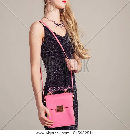 slim trendy woman in evening dress with pink bag in hands and stylish necklace on gray background
