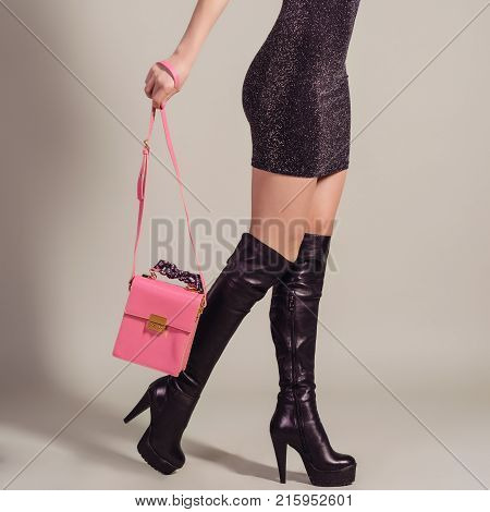 Woman sexy legs in jackboots with pink handbag. Shopping and business