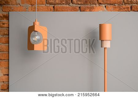 Two metallic orange lamps on the background of the gray panel and brick wall. One lamp is tall and has a wooden part, other is hanging on the cable and has an edison light bulb. Closeup. Horizontal.