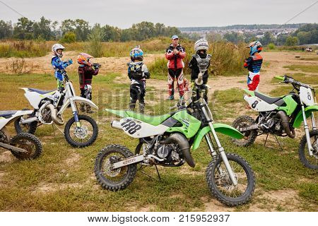 MOSCOW, RUSSIA - SEP 3, 2017: Trainer works with children motorcross team before main training outdoor.