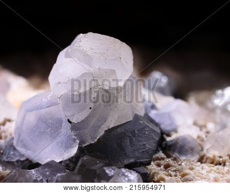 Closeup photograph of glittering transparent calcite stone crystal with purple details with black background. Natural phenomenon.