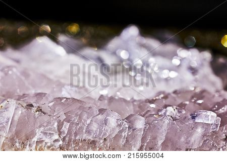 Closeup photograph of glittering transparent calcite mineral crystal with reddish details and very small part of black background. Natural phenomenon.