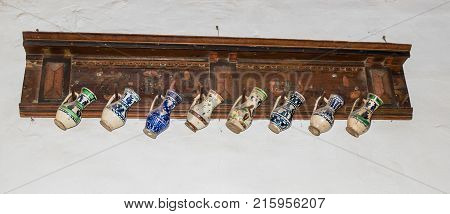 Sighisoara Romania October 08 2017 : Decorative jugs hanging on a decorative shelf in the Clock Tower in the castle of old city. Sighisoara city in Romania