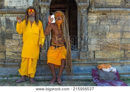 KATHMANDU, NEPAL - September 23, 201: Two Sadhu in Pashupatinath Temple, famous, sacred Hindu temple dedicated to Pashupatinath, located on the banks of the Bagmati River in Kathmandu.