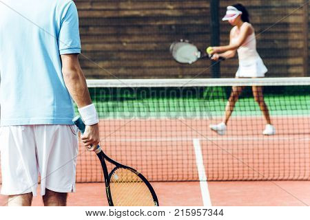 Who is going to win. Beautiful young couple playing tennis on the tennis court.