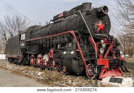 Kazakhstan Ust-Kamenogorsk november 2 2017: Old soviet locomotive next to the railway station. The station