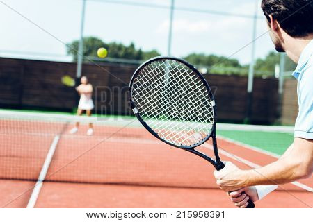 Beautiful competition. Rear view of young couple playing tennis on the tennis court.