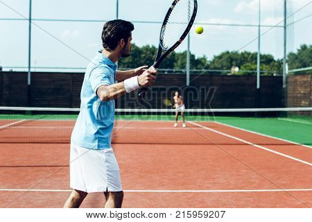 Perfect game together. Rear view of young couple playing tennis on the tennis court.