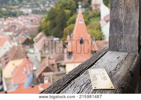Sighisoara Romania October 08 2017 : Pointer - Rome 1096 Km - nailed to the railing of the Clock Tower in the castle of old city. Sighisoara city in Romania