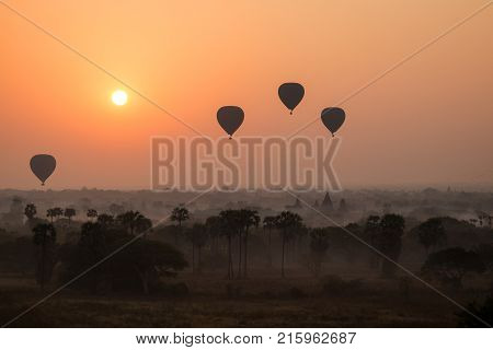 Silhouette of hot-air balloons over plain of Bagan at sunrise in Myanmar (Burma).