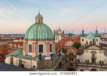 View of St. Francis of Assissi Church's dome and towers and other old buildings at the Old Town in Prague, Czech Republic, in the early evening from above.