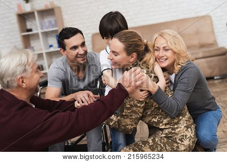 The family meets a woman in camouflage at home. She returned from the army. They are happy to see her. They embrace this woman. Her husband is disabled in a wheelchair.