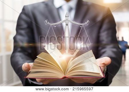 Lawyer shows the book and scales of justice on blurred background.