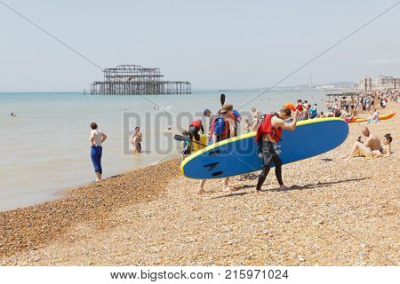 Brighton Great Britain - Jun 17 2017: Man With A Surfboard And Sunbathing People On The Brighton Bea