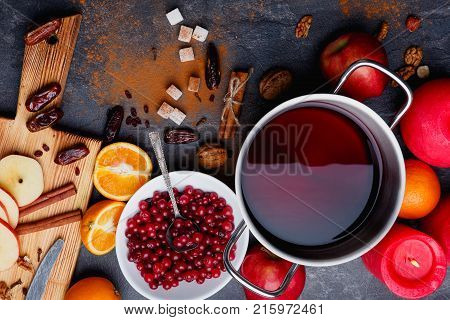 On the table are products for making mulled wine. Metal pot with fragrant mulled wine, deep plate with cranberries, oranges, apples, dates and grated cinnamon. View from above.