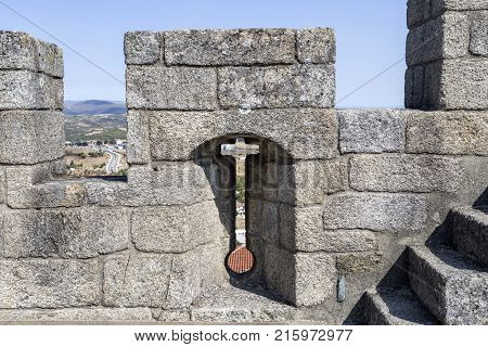 Arrow slit crosslet loop or an arbalestina in a merlon on top of the donjon also called the keep of the castle in Braganca Portugal