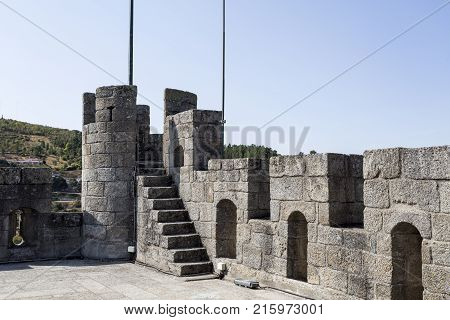 The cylindrical watchtower merlons and arrow slits on top of the donjon the keep of the castle in Braganca Portugal