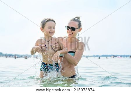 Young mother in black sunglasses and smiling baby boy son playing in the sea in the day time.