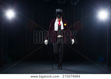 Magician, Juggler man, Funny person, Black magic, Illusion standing on the stage with a cane of beautiful light.