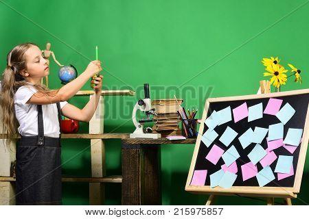 Schoolgirl With Proud Face In Classroom. Kid And School Supplies