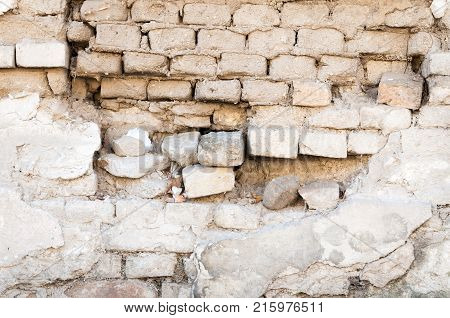 Bad foundation base on brick wall of old house or building with damaged plaster closeup