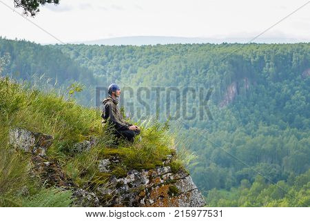 Happy man with eyes closed sitting on the edge of a cliff meditating in yoga pose , relax and leisure in harmony with nature
