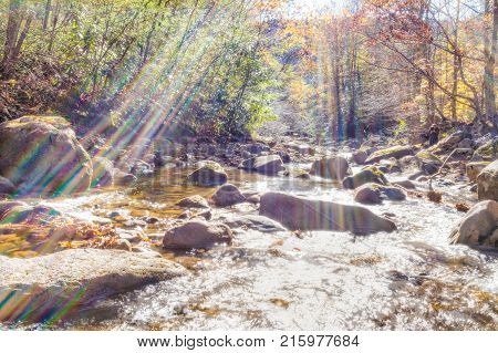 Closeup of shallow rock stream with running water stones and smooth flowing creek with rainbow flare