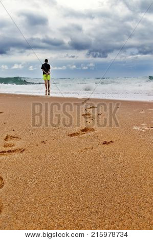 Traces on the sandy beach by the storming sea during bad weather. On border of sand and water there is a young man in shorts and looks at the sea. Traces conduct to the sea