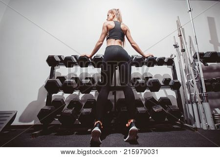Dumbbells. Girls are standing at the counter with dumbbells. Concept body fitness, workout.