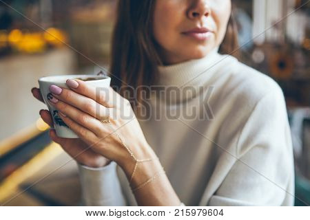 Close-up of woman hands holding cup of coffee in autumn / winter evening day. Morning drinking coffee and eating dessert. Relaxing mood break time