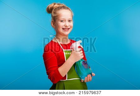 isolated on blue, cute girl in red sweater and olive apron with fair-haired updo, holding a cleanser spray, looking into the camera. copyspace.