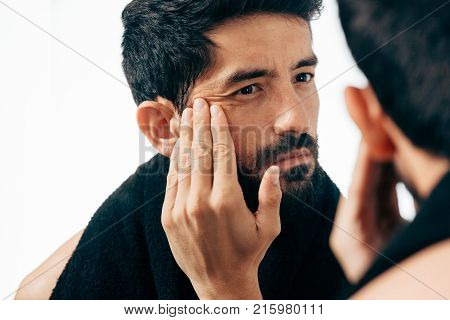 Man In Front Of Mirrror Looking At His Wrinkles