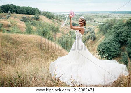 Portrait Of A Young Beautiful Bride On A Background Of A Gorgeous View Of The River And Fields.