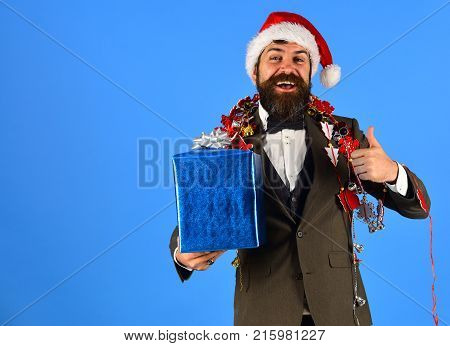 Businessman With Cheerful Face Holds Present Box Showing Thumbs Up.