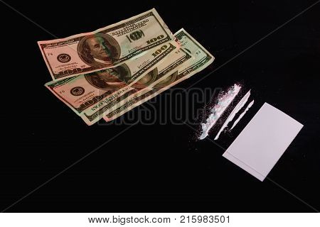 Near the white card are several strips of dosed cocaine and a few dollar bills. On a black background.