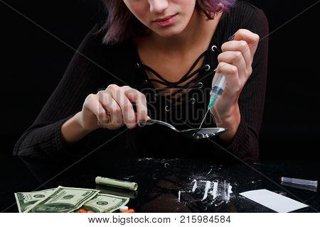 A drug addict young girl in a black sweater picks up the drug in a syringe from a spoon. Next to the table are tablets, dollar bills, a white card and scattered cocaine. On a black background.