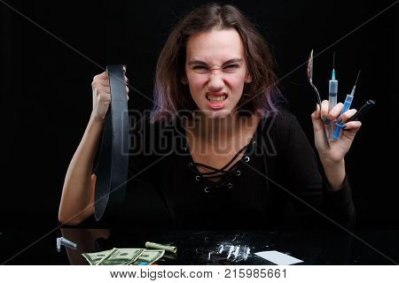 A young drug-dependent girl twists her face and holds a black, tight tourniquet, two syringes, a metal spoon and a lighter. Next to the table are scattered cocaine and cocoa dollies. On a black background.