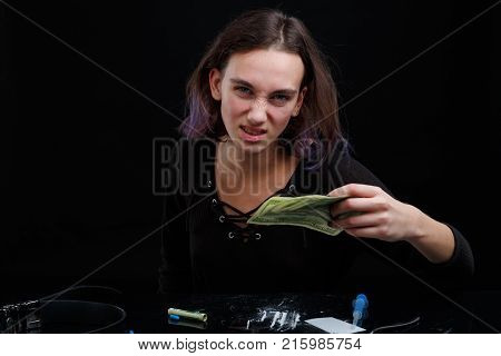 A drug addict aggressive girl holds several dollar bills in her hands, sitting at a table with scattered cocaine. On a black background.