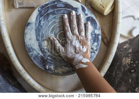 Dirty hand of potter in white clay on potter's wheel, top view