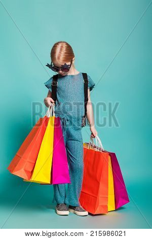 isolated on blue, red-haired girl in star-shaped sunglasses, blue overall and silver slip ons with a lustrous backpack, holding multicolored paper bags in both hands. copyspace.