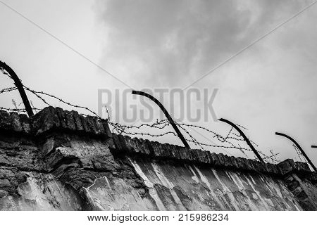 Ominous barbwired concrete wall of the concentration camp Terezin with storm clouds in the background - Black and White
