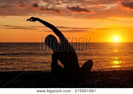 Girl Practicing Yoga On The Beach. View From The Back, Sunset, Silhouettes