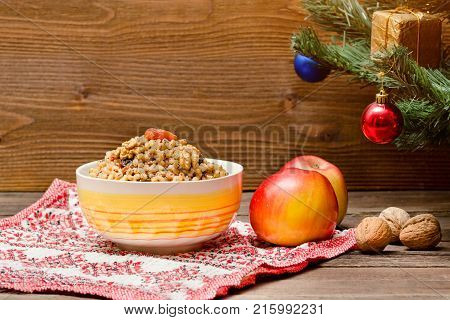 Dish Of Traditional Slavic Treat On Christmas Eve. Christmas Tree, Apples, Walnuts On A Patterned Ta