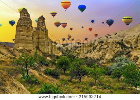 Hot Air Balloons Flying In Sunset , Mountain Landscape In Cappadocia, Turkey