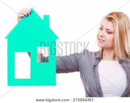 Dream about stabilization and family. Blonde girl holding green paper house model cutout. New flat apartment. Isolated on white