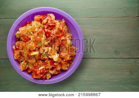 Stewed Tomatoes With Onions In A Plate On A Wooden Background