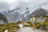 New Zealand backpackers tramping on Mount Cook / Aoraki Hooker valley travel. Backpacking hikers hiking on walking on Hooker Valley Track. Snow capped mountains glacier landscape. Couple on adventure. poster