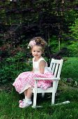 Little girl poses for picture on Easter Sunday morning. She is wearing a pink and white gingham dress and curly ribbon hairbow. She is sitting in a white wooden rocking shair and smiling. poster